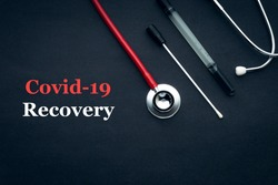 COVID-19 or CORONAVIRUS RECOVERY text with stethoscope and medical swab black background. Covid-19 or Coronavirus concept.
