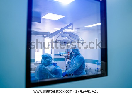Covid-19 outbreak. Healthcare worker. Doctors working in intensive care unit. Professional intensive care system in the background. View from the window to the operating room. Photo stock ©