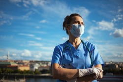 covid-19 pandemic. confident modern physician woman in scrubs with stethoscope, medical mask and rubber gloves looking into the distance outdoors in the city against sky.