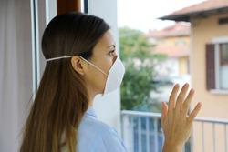 COVID-19 Pandemic Coronavirus Woman home isolation auto quarantine wearing face mask protective for spreading of disease virus SARS-CoV-2. Girl isolation mask on face against Coronavirus Disease 2019.