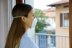 COVID-19 Pandemic Coronavirus Woman home isolation quarantine wearing face mask protective for spreading of virus SARS-CoV-2. Professional nurse looking through the window worried into hospital.