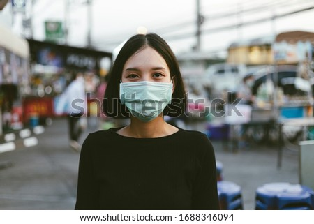 COVID-19 Pandemic Coronavirus Woman in city street wearing face mask protective for spreading of disease virus SARS-CoV-2. Girl with surgical mask on face against Coronavirus Disease 2019.