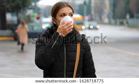 COVID-19 Pandemic Coronavirus Woman in city street wearing protective face mask for spreading of disease virus SARS-CoV-2. Girl with protective mask on face against Coronavirus Disease 2019.