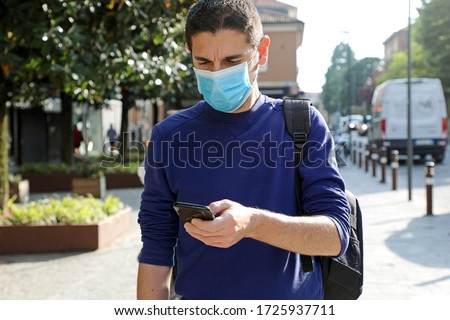 COVID-19 Pandemic Coronavirus Worried Young Man Wearing Surgical Mask Using Smart Phone App in City Street to Aid Contact Tracing and Self Diagnostic in Response to the Coronavirus Pandemic 2019