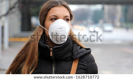 COVID-19 Pandemic Coronavirus Young Girl in city street wearing face mask protective for spreading of Coronavirus Disease 2019. Close up of young woman with protective mask on face against SARS-CoV-2.