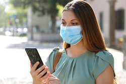 COVID-19 Pandemic Coronavirus Young Woman Wearing Surgical Mask Using Smart Phone App in City Street to Aid Contact Tracing in Response to the Pandemic Coronavirus