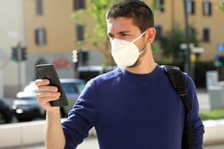COVID-19 Pandemic Coronavirus Young Worried Man Wearing KN95 FFP2 Mask Using Smart Phone App in City Street to Aid Contact Tracing and Self Diagnostic in Response to the Coronavirus Pandemic 2019