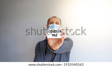 COVID-19 pas symbol. White card with words 'COVID-19 pas'. A young man in a grey wear and medical mask. Sunshine. Beautiful white background. COVID-19 pas coronavirus concept. ストックフォト ©