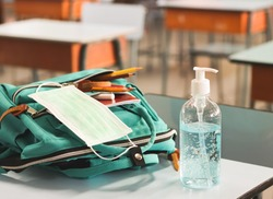 COVID-19 prevention , back  to school  and new normal  concept.Front view of  sanitizer gel and  surgical mask in backpack with school supplies  on school desk in classroom.