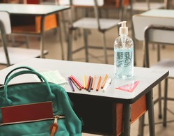 COVID-19 prevention , back  to school  and new normal  concept.Sanitizer gel bottle ,school supplies and surgical mask on school desk in classroom.