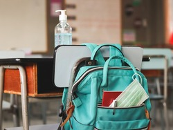 COVID-19 prevention , back  to school  and new normal  concept.School backpack with school supplies and medical face mask hanging with chair with alcohol gel on desk in classroom.