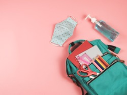 COVID-19 prevention while going back  to school  and new normal  concept.Top view of backpack with school supplies , blue polka dot fabric masks and sanitizer gel on pink background.