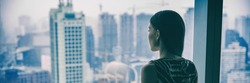 COVID-19 Quarantine mental health. Woman self isolated at home pensive looking out of high rise building window at city skyline thinking of relationship, employment, coronavirus. Panoramic banner.