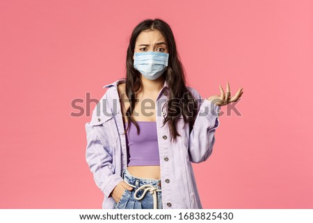 Covid19, quarantine, people concept. Confused young girl shrugging, look clueless why people going outside during coronavirus pandemia outbreak, wear medical face mask, pink background