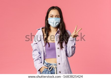 Covid19, quarantine, people concept. Optimistic, smiling happy girl in medical face mask, inside home, show peace sign, encourage stay safe during coronavirus pandemia outbreak, pink background