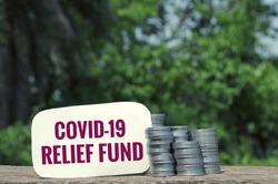 Covid-19 Relief Fund Tag With Stack of Coin on Wooden Surface in Horizontal Orientation
