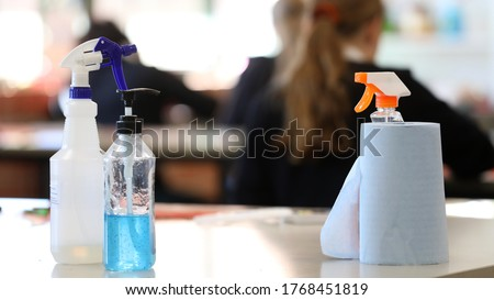 Covid safe school. Inside a classroom with cleaning products on display such as hand sanitizer, disinfectant, paper towel on a desk. Corona virus issues and impact. Deliberate blurred students