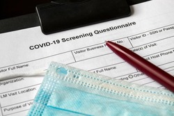 COVID-19 Screening Questionnaire form with medical mask and a pen on it. Healthcare and medical concept. Closeup