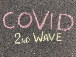 COVID second wave hand written text with sidewalk chalk on the grey asphalt, corona virus second wave, pandemic