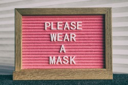 COVID-19 sign PLEASE WEAR A MASK at grocery store entrance for coronavirus prevention. Message on pink felt letter board. Compulsory measure in businesses for face protection wearing.