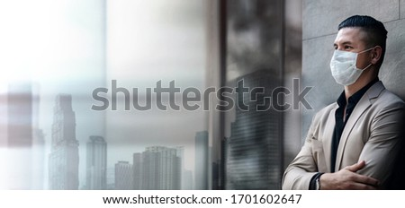 Covid-19 Situation in Business Concept. Businessman with Safety Surgical Mask standing at Office City Building. Employees or Owner Protected and Care of Health. Stressed out due to Corona Virus