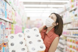 covid-19 spreading outbreak. Woman in medical protective mask panic buying tissue paper. Fear of coronavirus.