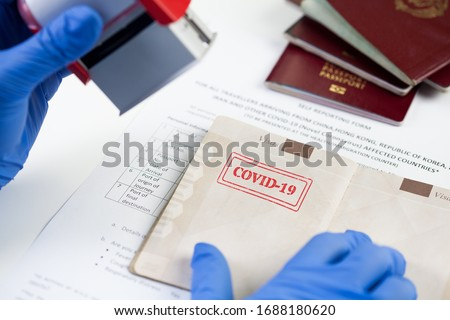 COVID-19 stamped in passport,airport border customs health and safety security check,restrictive no entry measures due to SARS-CoV-2 corona virus disease epidemic,Coronavirus global pandemic,US & UK
