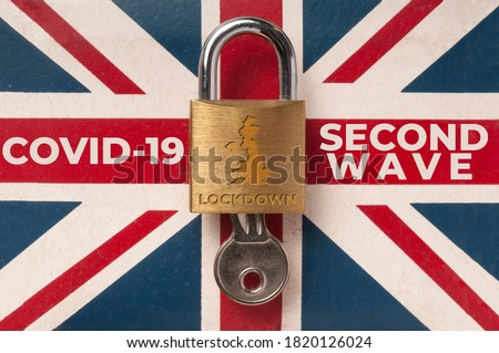 "Covid-19 UK lockdown concept: a lock over a union jack flag with the message ""second wave lockdown"""