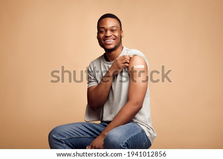 Covid-19 Vaccinated African Man Showing Arm With Plaster, Beige Background Stock photo ©