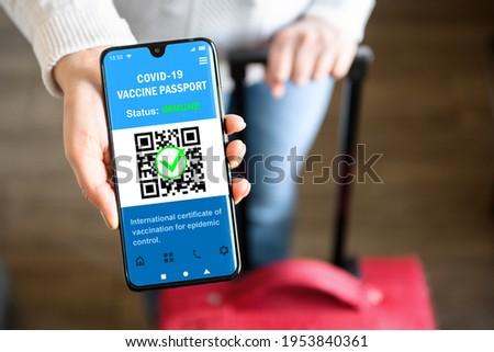 COVID-19 vaccination passport in mobile phone for travel, tourist holds smartphone with health certificate app, digital coronavirus pass. Concept of corona virus, immunity passport and tourism.