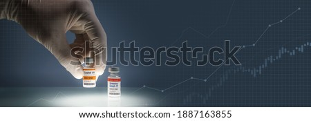 Covid-19 Vaccine Research and Development concept. Hand of a researcher select and pick up a SARS-CoV-2 vaccine vial from potential candidates with index chart graphic as the background. Banner.