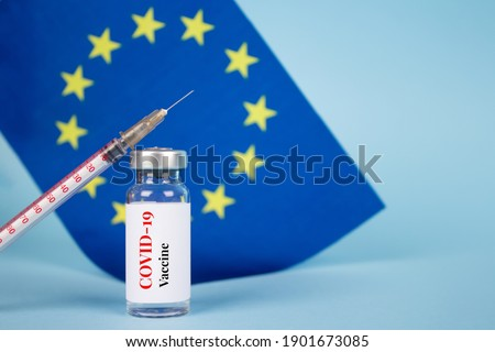 COVID-19 vaccine vial against EU flag on blue background with copy space for text - coronavirus vaccine doses, europe vaccination concept, selective focus