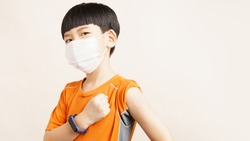 COVID 19 Vaccines for Kids concept. Studio portrait of an adorable asian boy with medical face mask just got his first dose vaccine. Authorized, Approved, Trial, Safe, Available, Back to school.