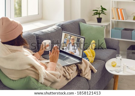 Covid-19 virus, flu or common cold consultation via online medical video chat. Sick woman wrapped in blankets sitting on sofa at home, making Skype call to eHealth doctor and waving hand at laptop
