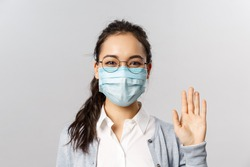 Covid19, virus, health and medicine concept. Portrait of friendly young girl in medical face mask saying hi, hello waving hand and grinning with eyes, keep safe during pandemia, quarantine