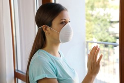 COVID-19 Woman home isolation auto quarantine wearing face mask protective for spreading of disease virus SARS-CoV-2. Girl voluntary isolation surgical mask on face against Coronavirus Disease 2019.