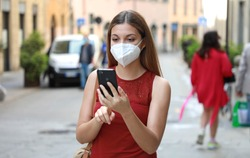 COVID-19 Woman in city street wearing KN95 FFP2 mask against disease virus SARS-CoV-2 and using Smart Phone App to aid contact tracing and self diagnostic in response to Coronavirus Disease 2019