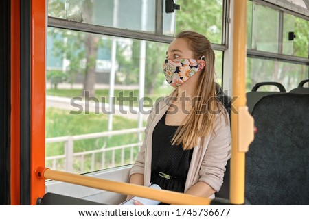 Covid 2019, young woman with respiratory mask traveling in the public transport by bus. Unique protective mask of the respiratory tract from coronavirus.