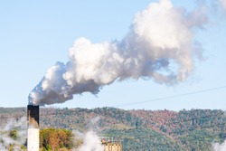 Covington, Virginia city in Alleghany county small town and pollution from paper mill smokestack closeup against sky