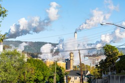 Covington, Virginia city in Alleghany county small town and smog pollution from paper mill smokestack during autumn day