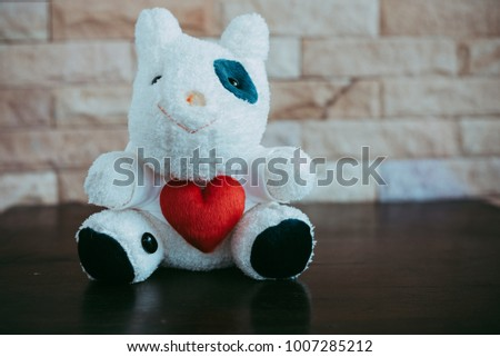 Cow doll holding a red heart shape, Valentine 's Day concept. #1007285212