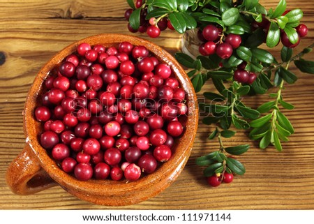 Cowberries in ceramic pot on wooden background.
