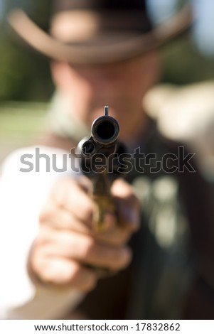 Cowboy aiming gun, focus only on gunpoint