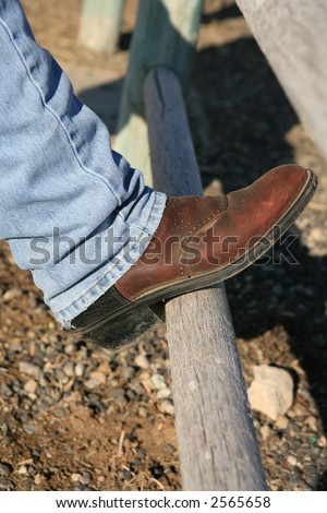 Cowboy boot blue jeans on wood pole fence