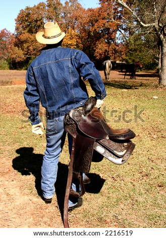 Cowboy carrying saddle