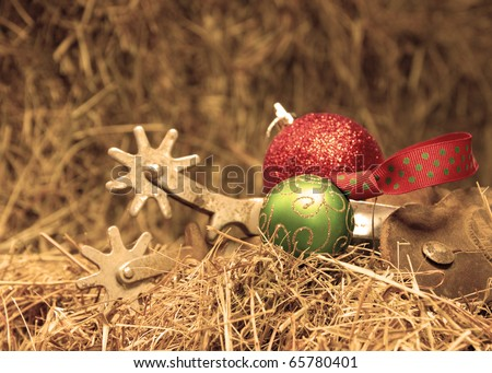Cowboy Christmas - Christmas ornaments with a set of old rusty spurs on hay in sepia tone