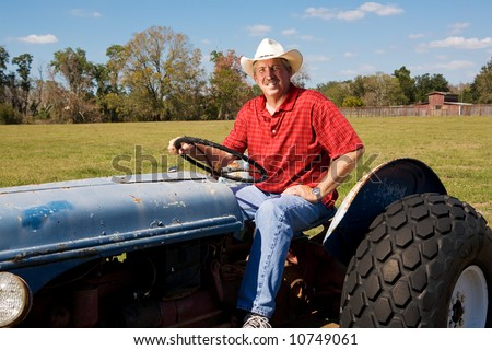 Cowboy farmer riding in his tractor