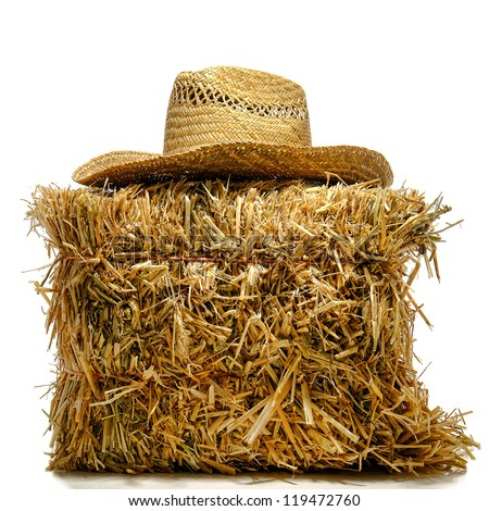 Cowboy farmer traditional hat on top of a bale of straw hay over white