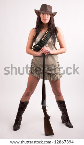 Cowboy girl. Art shot of a pretty model with shotgun.