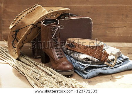 Cowboy hat and accessories against a wood textured background